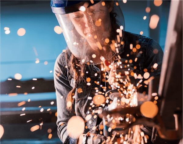 woman wearing mask and welding with sparks flying