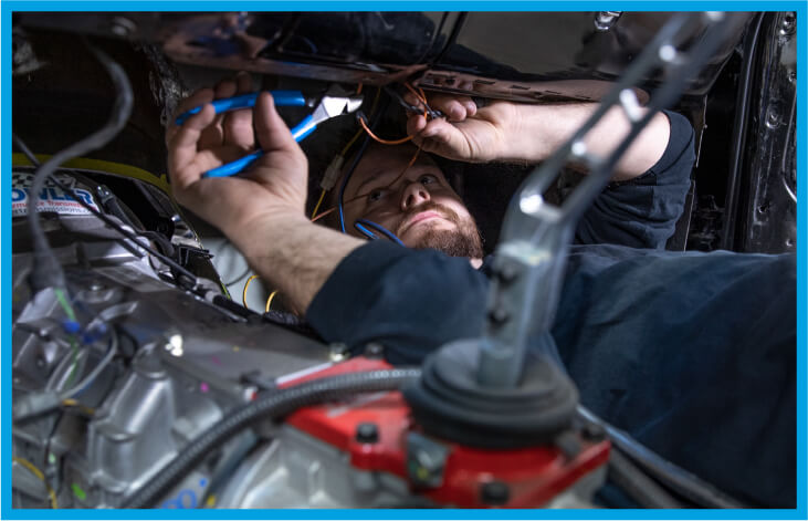 A pro using a tool on the underside of a car